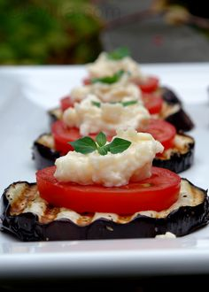 Grilled eggplant slices topped with tomato slices, garlicky parmesan sauce, and fresh herbs