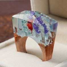 THE HEAVENS KNOW THAT PERFECTION CAN ONLY BLOOM IN DELICACY  This ring is made of clear resin and pink blossoms. The base is a light oak wood, a dense and incredibly strong wood.