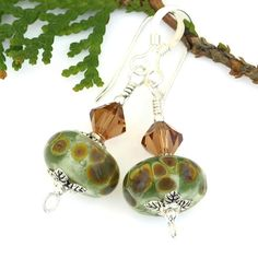 Reminiscent of the ethereal, whispering beauty of a forest just beginning to leaf out in the spring, the one of a kind WHISPERS earrings are an earthy combination of light mossy green and rich brown. The one of a kind, handmade beauties were created with artisan handmade lampwork glass beads, Swarovski crystals, leafy pewter bead caps and sterling silver.