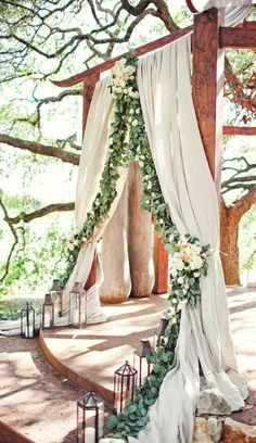 Outdoor wedding arch decorated with drapes and eucalyptus leaves. See more French inspired #wedding decor here: http://www.mywedding.com/articles/french-wedding-decor-details/