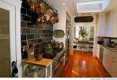 tyler florence's REAL kitchen.. I love the copper cookware (Mauviel, I think), the green subway tile, the wood floor, the refrigerator, the casualness... ooh, and the skylight