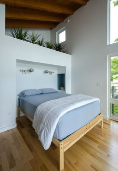 Cubbies take the place of bedside tables. The plants above help to visually separate the open closet space behind the bed.