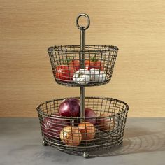 "Shop Rustic 2-Tier Iron Fruit Basket.  Tiered display and serving baskets are handcrafted of iron wire in a distinctive rustic ""weave"" and finished in a multistep process of zinc plating, dipping and rubbing to create the beautiful, dark antiqued patina."