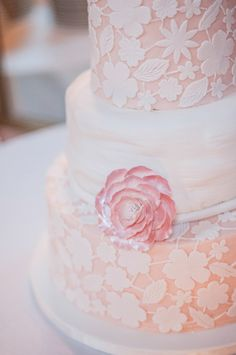 Pink tiered wedding cake with white fondant flower accents, featured on The Pink Bride www.thepinkbride.com {Top 10 Questions to Ask Your Wedding Cake Baker}