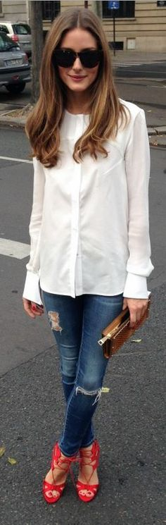 Who made  Olivia Palermo's white long sleeve top, brown clutch handbag, blue skinny jeans, black sunglasses, and red lace up sandals?