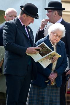 Queen Elizabeth looks at a racing program while at a horse event.