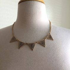 Triangle necklace Dainty and stylish! It's a good triangle necklace. The triangles have black designs in them. Gold chain. Worn a couple times. Jewelry Necklaces