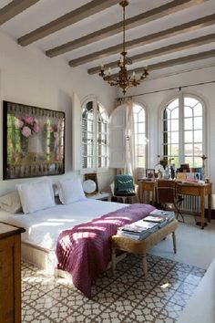 [ Maria Llado ] -- arched windows, wooden beams on white ceiling, table for memories and letter writing