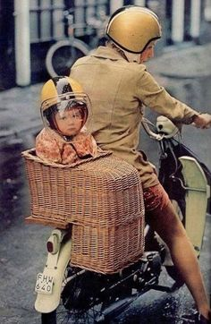 Photo of a #child riding in a #basket seat on the back of a Vespa scooter. At least he is wearing a helmet. They sell those baskets now to put on the stairs!!