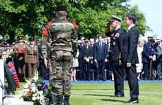 6/6/14. Tribute: The Prince of Wales lays a wreath on the war memorial at the Commonwealth War Graves Cemetery in Bayeux before saluting next to PM Manuel Valls