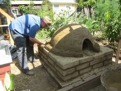 Kurt adds the insulation layer. You can see the base--made out of adobe bricks I made in the backyard.