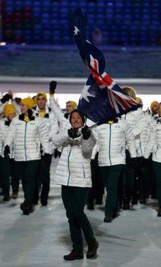 Snowboarder Alex Pullin carries the Australian flag into the stadium at the Opening Ceremony of the 2014 Sochi Winter Olympics.