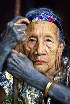 "Malaysian Dangah Anyit, believed to be 80, sits in Sungai Asap village, in the upriver area in the interior of state of Sarawak on the Borneo island, on December 10, 2003. Dangah belongs to Kenyah, a former headhunting tribe, said to be descendants of Bornean aborigines. The Kenyah, an ""orang ulu"", a phrase literally means ""upriver people"", live in a village consists of a 400-yard longhouse built on piles, with a row of family rooms at the back and a wide covered veranda that serves as a…"