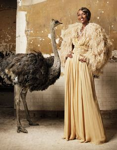 An ostrich and a lovely lady in a draping and feathered gown, sporting a 20's style hair-style.