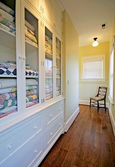 Upstairs hallway has built-in glass front display cabinets for quilts with storage drawers beneath.