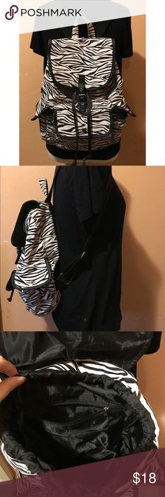 Black and White Zebra Print Drawstring Backpack A cute drawstring style backpack with a black and white zebra pattern. Inside has a solid black lining. Condition: Very good condition overall except there is a slight stain on the handle and below that as seen in photos but will be cleaned before shipping.  -button closure  -adjustable straps  -1 wide front pocket, 2 side pockets and 1 zippered pocket inside. Bags Backpacks