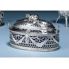 AN IRISH SILVER BUTTER DISH AND COVER, EDWARD BOYCE, DUBLIN, CIRCA 1775 of oval tub form, the sides pierced with pales and scrolling foliage and chased with swags, engraved with contemporary crest, matching domed cover with couchant cow finial, marked on base rim and cover