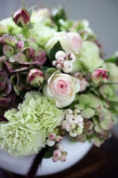 Snowberries, pierre spray garden roses, mint green carnations, and antique hydrangea