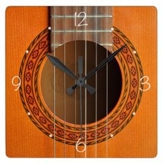 A close up photo of the decorated rosette around the sound hole of a classic guitar, with an inlaid pattern in red, black and green on tan colored wood, with frets and nylon strings. #guitars #classical #spanish #inlay #acoustic #music #musician #musical #instruments #musicians