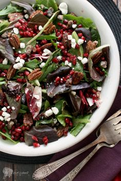 Pomegranate Salad | Spring greens tossed with candied pecans, dates, pomegranate arils and goat cheese ... dressed in a pomegranate vinaigrette! Gorgeous for the holidays and just bursting with flavor! | from Girli Chef