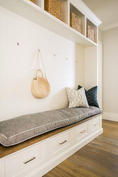 Overhead shelves holding wicker bins are mounted above nickel coat hooks fixed to a shiplap trim positioned over a long white storage bench fitted with a wood top and a gray linen cushion.