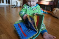 """Great """"Busy Book"""" for toddlers. Very clever idea using grommets and different clasps, also family pictures."""