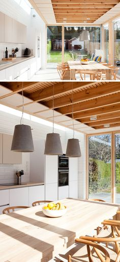 This modern house extension includes a dining table and a kitchen. Three concrete pendant lights anchor the dining table and chairs in the room. Minimalist Dining Room, Modern Minimalist, Dublin, Charred Wood, Glass Extension, Timber Cladding, Dining Table Chairs, Dining Rooms, Interior Lighting