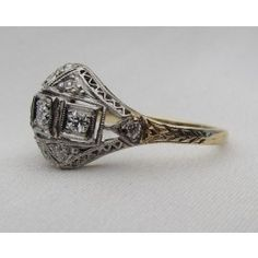Circa 1930. This striking Art Deco ring is centered by three Old European cut diamonds with a .20 carat total diamond weight, SI1-SI2 clarity and G-H color. Eight single cut diamonds accent the center stones with a .24 carat total diamond weight, VS2-SI1 clarity and G-H color. The platinum topped 18KT yellow gold ring is handmade.  Appraised Value: $3,600.