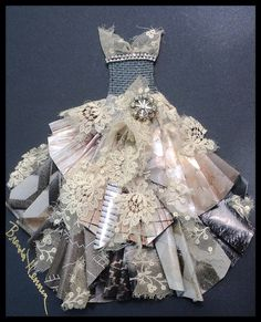 Paper dress number 6 by Brenda Henning.  Folded paper accented by torn vintage lace---vintage earring added