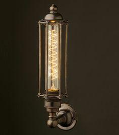Eine längliche Glühbirne dient als Wandleuchte im industriellen Stil