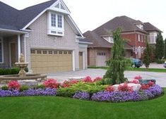 A water fountain in the middle of the brick entryway is a nice touch to this home. The garden bed in front adds colour and contour to the front yard.  Picture compliments of www.ogslandscape.ca