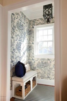 Chic blue mudroom features walls clad in Lee Jofa Willow Pattern Blue Wallpaper lined with a white chinoiserie bench illuminated by a black pagoda lantern.