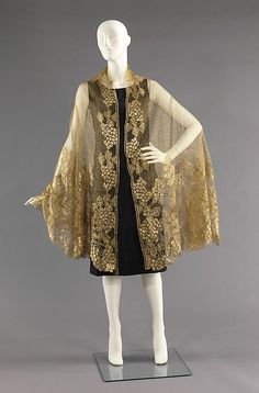 Embroidered silk and metallic mesh evening shawl, French, ca. 1925. This shawl captures the opulence and decorativeness of the Art Deco period. Interest is added to the graceful pattern by the motifs encroaching upon the mesh central field, adding movement and vitality to the appearance. Perhaps what makes this garment even more special is its remarkable condition, for metallic lace is often tarnished.