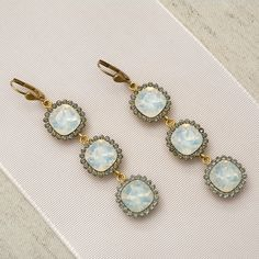 Three white opal crystals surrounded by small black diamond crystals, set in antique gold. Perfect winter time sparkle for nights out, as well as a dazzling bridal earring.  Designed by Catherine Popesco for La Vie Parisienne. I
