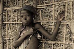 Retrato de una niña adolescente con un tatuaje facial, menos marcado que los que llevan las mujeres de más edad de su mismo clan.