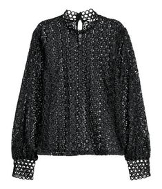 Black. Lace blouse with a small stand-up collar, opening and button at the back of the neck and long sleeves with buttoned lace cuffs. Unlined.