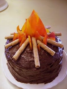 Camp Fire Cake... Crush 5 red hard cinnamon candies & 5 hard butterscotch, bake in sprayed baking sheet @ 350 for 6-8 mins. Cool completely and break into shards for flame. Pretzel rods or pirouettes for logs.