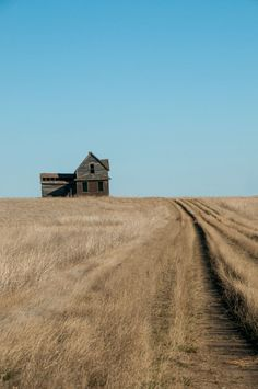 old house on the prairies with a blue sky and a prairie trail