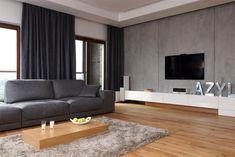 Drewniane podłoga i minimalistyczny stolik kawowy są kontrapunktem dla szarości, która występuje w tym salonie w kilku różnych odcieniach. A miękki dywan typu shaggy równoważy szorstką fakturę betonowych płyt na ścianie. W podwieszanym suficie zamontowany został rozwijany ekran do rzutnika.
