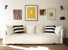 white couch, black and white stripe cushions, colorful accents