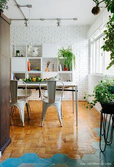 Sala de jantar tem mesa branca com cadeira Eames e Tolix e estante com nichos.