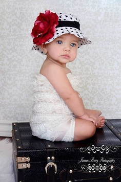 White hat with black polka dots Sun Hat by Fancy That Hat, embellished with a black sash and red flower.