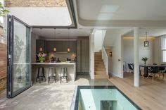 Brackenbury House by Neil Dusheiko Architects is the dramatic reshaping of a home for a young family in a strict conservation zone in west London. The house incorporates a glass floor and doors that peel back to open up the corner of the house to the outdoors.