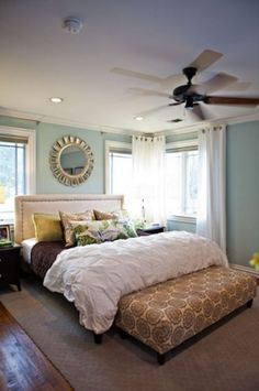 Master bedroom - upholstered headboard, and bench at end of bed, large circle mirror above headboard, ceiling to floor drapes and big puffy white comforter