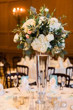A tall wedding table centerpiece with greenery, white hydrangeas, and pink and white roses | Gretchen Wakeman Photography | villasiena.cc