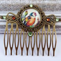 Hair comb made of bronze metal with a setting with handmade glass cabochon. The cabochon shows a beautiful animal motif with bird. The comb is decorated with swarovski rhinestones in light green and brown. He has the dimensions 5.7 L x 6.5 W cm.   MATCHING EARRINGS OR JEWELRY SETS YOU WILL ...