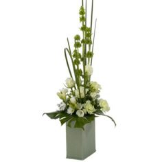Modern tall arrangement with white roses, freesias and malucca balm