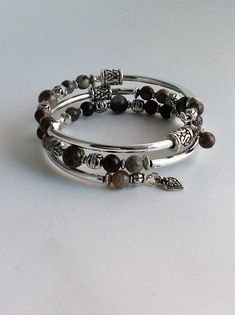 This wrap bracelet is made with silverplated memory wire and consists of 2 sizes of Pietersite gemstone beads and a variety of silver-tone and pewter spacer beads. A charm and bead dangle complete the bracelet ends. A memory wire bracelet is the perfect gift for yourself or someone