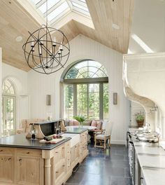 "Contemporary Kitchen with slate tile floors, Signature hardware 30"" reinhard fireclay farmhouse sink, Chandelier, can lights"