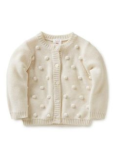 100% cotton cardi with all over matching pom poms and centre front button opening